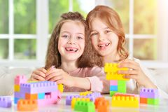 Little girls playing with plastic blocks. Two cute little girls playing with colorful plastic blocks Stock Image