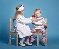 Two cute little girls playing doctor Stock Images