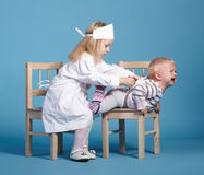 Two cute little girls playing doctor Stock Photo