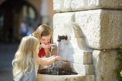 Two cute little girls playing with a drinking water fountain on warm and sunny summer day Royalty Free Stock Photos