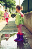 Two cute little girls playing and having fun on the street, in an autumn day. retro filtered image Royalty Free Stock Photo