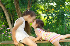 Two cute little girls playing at the park stock images
