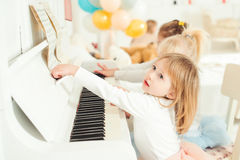 Two cute little girls playing piano in a studio. Stock Photos