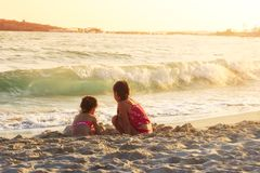 Two Cute Little Girls playing with sand by the Sea Waves at suns. Et. Summer Sunny Day, Ocean Coast, happy children concept royalty free stock images