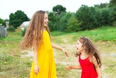 Two beautiful little girls playing and smiling at sunny summer d. Two cute little girls playing and smiling at sunny summer day outdoors. Happy childhood concept Stock Photography