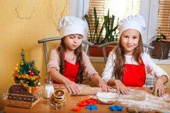 Two cute little girls preparing Christmas cookies in the kitchen at home royalty free stock photo