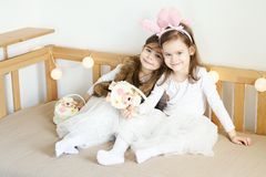 Little girls in rabbit ears sit on the couch with Easter baskets. Two cute little girls in rabbit ears are sitting on the sofa with Easter baskets Stock Photography