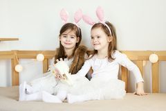 Little girls in rabbit ears sit on the couch with Easter baskets. Two cute little girls in rabbit ears are sitting on the sofa with Easter baskets Royalty Free Stock Photography