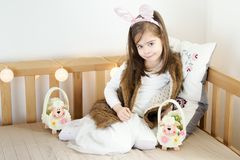 Little girls in rabbit ears sit on the couch with Easter baskets. Two cute little girls in rabbit ears are sitting on the sofa with Easter baskets Stock Photo