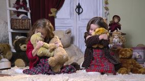 Two girls in dresses hug plush toys sitting on a nap carpet, slow motion stock video footage