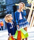 Two cute little girls with shopping bags in city Royalty Free Stock Photo