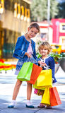 Two cute little girls with shopping bags in city Royalty Free Stock Images