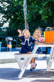 Two cute little girls with shopping bags in city Stock Photo