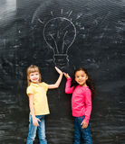 Two cute little girls showing drawn lamp with hands Stock Image