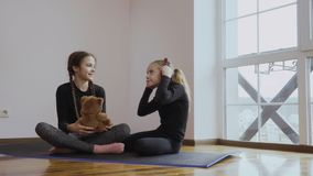 Two little sisters listens music in headphones. Two cute little girls sits on floor on the carpet. Older girl listens music in headphones and her sister takes stock footage