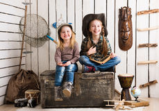 Two cute little girls sitting on big wooden chest Royalty Free Stock Photography