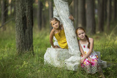 Two cute little girls sitting on an old pedestal Royalty Free Stock Images