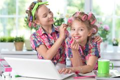 Cute little girls beautifying themselves. Two cute little girls sitting at table with laptop and beautifying themselves Stock Images