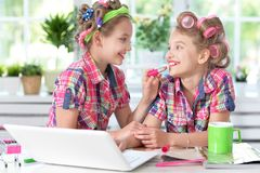 Cute little girls beautifying themselves. Two cute little girls sitting at table with laptop and beautifying themselves Stock Photography