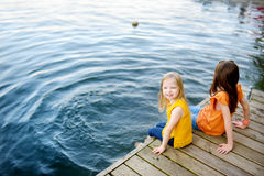 Two cute little girls sitting on a wooden platform by the river or lake. Dipping their feet in the water on warm summer day Stock Images