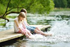 Two cute little girls sitting on a wooden platform by the river or lake dipping their feet in the water on warm summer day. Family activities in summer royalty free stock image