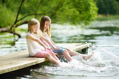 Two cute little girls sitting on a wooden platform by the river or lake dipping their feet in the water on warm summer day. Family activities in summer royalty free stock photography