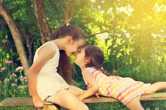 Two cute little girls smiling and playing at the park. Toned. Royalty Free Stock Images