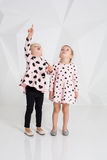 Two cute little girls standing in pink clothes with black hearts on the white wall background in the studio. Royalty Free Stock Image