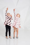 Two cute little girls standing in pink clothes with black hearts on the white wall background in the studio. Royalty Free Stock Photos