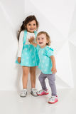 Two cute little girls standing in turquoise wear on the white wall background in the studio. Royalty Free Stock Images