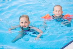 Two cute little girls in swimming pool Stock Photo