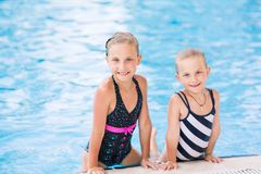Two cute little girls in swimming pool Royalty Free Stock Images
