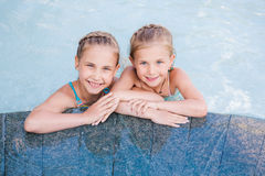 Two cute little girls in swimming pool Stock Image