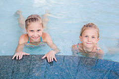 Two cute little girls in swimming pool Stock Photos
