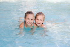 Two cute little girls in swimming pool Royalty Free Stock Photos
