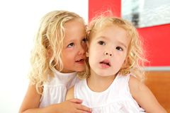 Two cute little girls together at home. Close up portrait of two cute little girls together at home stock photo