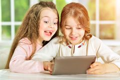Little girls using tablet. Two cute little girls using digital tablet Royalty Free Stock Image