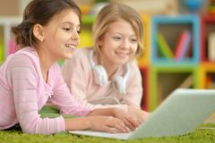 Little girls using laptop. Two cute little girls using laptop together Royalty Free Stock Photo