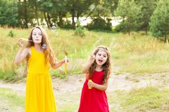 Two Cute Little Girsl blowing soap bubbles outdoor at sunny sum Stock Image