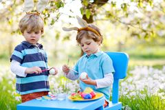 Two cute little kid boys wearing Easter bunny ears, painting colorful eggs and having fun outdoors. Family, siblings royalty free stock photos