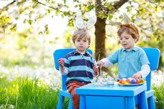 Two cute little kid boys wearing Easter bunny ears, painting colorful eggs and having fun outdoors. Family, siblings stock images