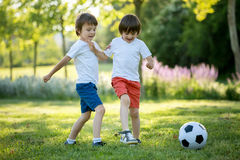 Two cute little kids, playing football together, summertime. Chi Stock Photography