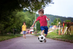Two cute little kids, playing football together, summertime stock photo