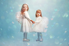 Two cute little sisters with an angel's wings Royalty Free Stock Photo
