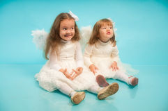 Two cute little sisters with an angel's wings Stock Images