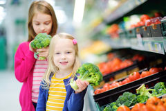Two cute little sisters choosing broccoli in a food store or a supermarket Royalty Free Stock Photo