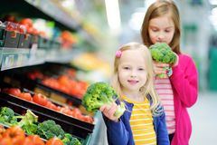 Two cute little sisters choosing broccoli in a food store or a supermarket Stock Photos