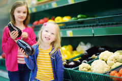 Two cute little sisters choosing eggplants in a food store or a supermarket Royalty Free Stock Image