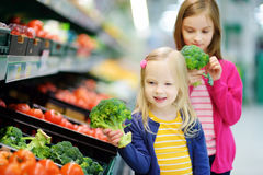 Two cute little sisters choosing fresh broccoli in a food store. Or a supermarket Stock Photo