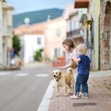 Two cute little sisters and a dog Stock Image